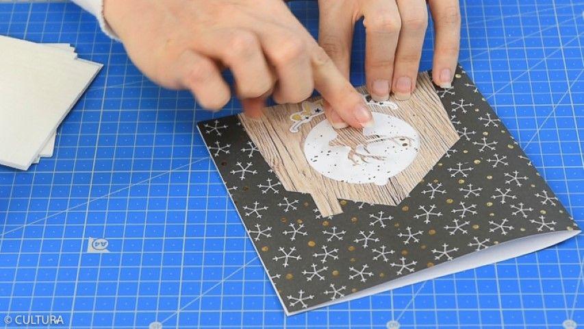 5. Coller à l'arrière de la couverture de la carte un carré de papier de 14 x 14 cm (motifs visibles au travers du médaillon). Fermer la carte. Enlever du motif cerf obtenu dans l'étape précédente, le contour médaillon pour ne conserver que le motif cerf. Coller en relief le motif cerf au centre du médaillon à l'aide des carrés de mousse adhésifs. Personnaliser la carte d'une forme de découpe.