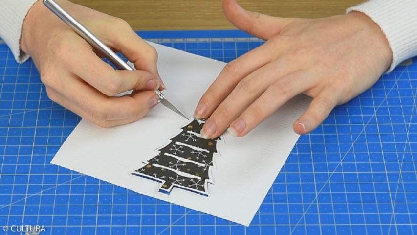 Découper plusieurs sapins et un cerf à l'aide de la machine et des matrices de découpe, comme expliqué précédemment. Varier les papiers et couper la base de certains sapins pour créer différentes hauteurs. Pour créer des sapins décorés sur les deux faces, coller les sapins au dos des papiers de la collection et découper le contour en laissant une marge blanche de quelques millimètres.