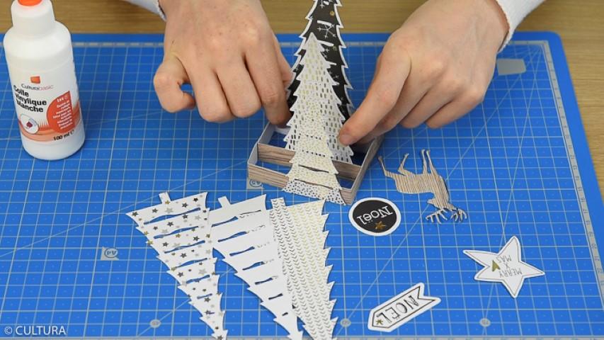 Coller harmonieusement les sapins et le cerf sur les bandes de la base carrée. Finaliser la décoration par une forme de découpe de la collection.