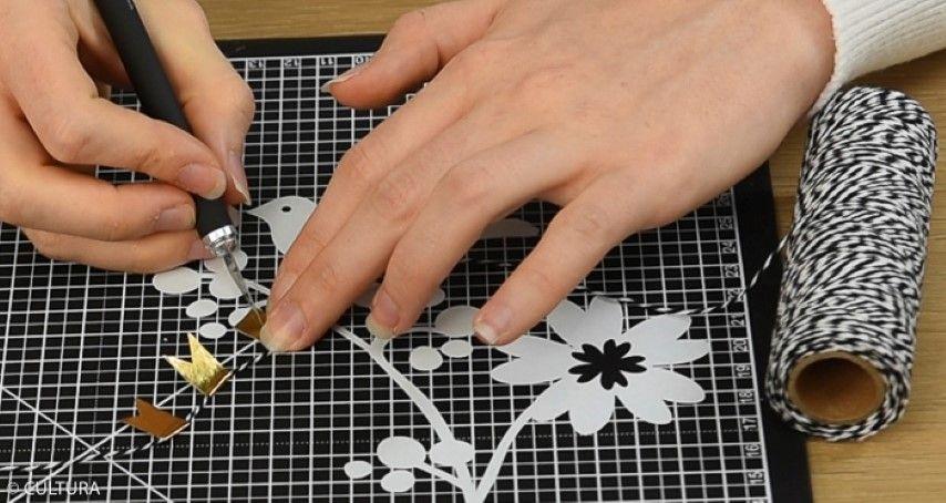 Personnaliser les enveloppes : 1. Pour créer une guirlande de fanions, doubler des morceaux de masking tape sur une ficelle bicolore. Couper les extrémités pour créer les fanions. Personnaliser les enveloppes d'une guirlande et des stickers de la collection. Coller les plis de l'enveloppe sur le sachet kraft.