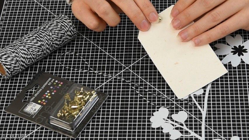 Personnaliser les étiquettes « tag » : Entailler le haut des tags avec un cutter de précision, insérer une attache parisienne et bloquer une longueur de ficelle bicolore. Personnaliser les tags de stickers de la collection et de petits messages. Les insérer dans les enveloppes sur les sachets kraft.