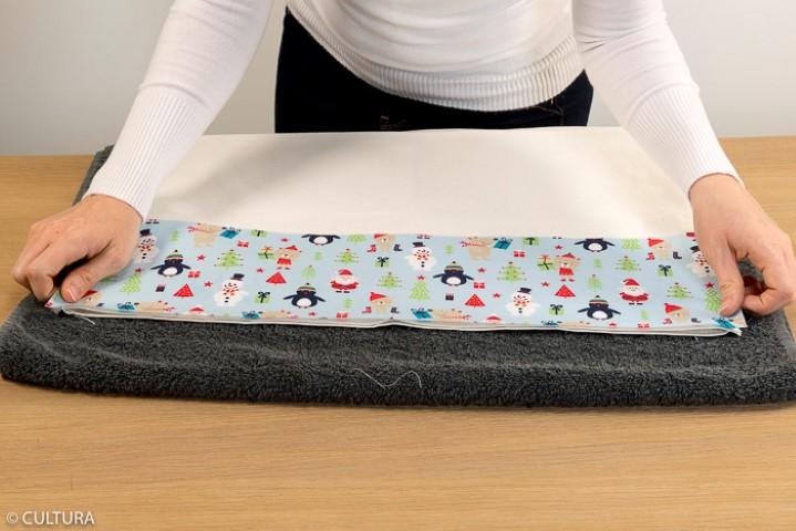 2. Retourner le sac sur l'envers. Veiller à positionner les bandes de tissu avec les motifs « tête en bas » pour qu' ils soient dans le bon sens lorsque le rabat de la hotte sera retourné.