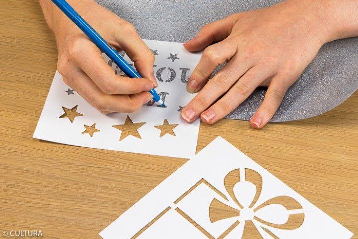 6. Reporter les détails du motif cadeau (noeud, ruban…), les étoiles et le mot « Joyeux Noël » des pochoirs au dos du thermocollant pailleté argent. Découper minutieusement les motifs.