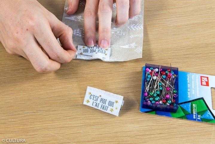 3. Placer et épingler l'étiquette « C'EST MOI QUI L' AI FAIT » sur l'endroit de la pièce (3b) comme indiqué sur le schéma et coudre à 0,5 cm du bord. Retirer l'épingle.