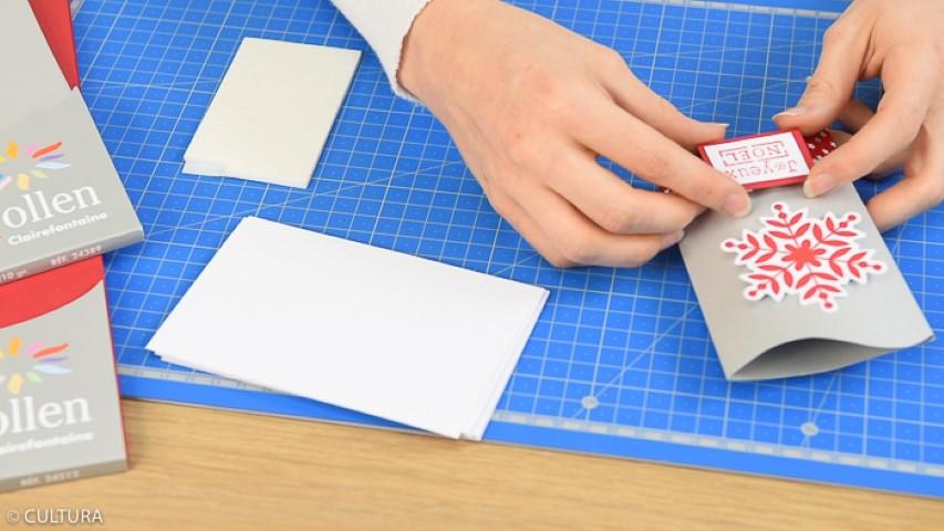 3. Créer une étiquette Joyeux Noël : enduire le tampon d'encre rouge et l'appliquer sur la carte blanche. Découper son contour et repositionner sur un papier rouge. Découper les bords pour obtenir une marge de quelques millimètres et positionner l'étiquette en relief à l'aide des carrés de mousse 3D.