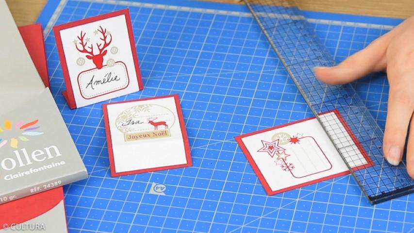 Création du marque place : Coller un sticker étiquette sur une carte blanche. Couper les bords en laissant une marge de 2 cm sous le sticker. Coller la carte sur un papier rouge et découper les bords pour obtenir une marge de quelques millimètres. Marquer un pli à 2 cm sous le sticker et plier pour obtenir le chevalet.