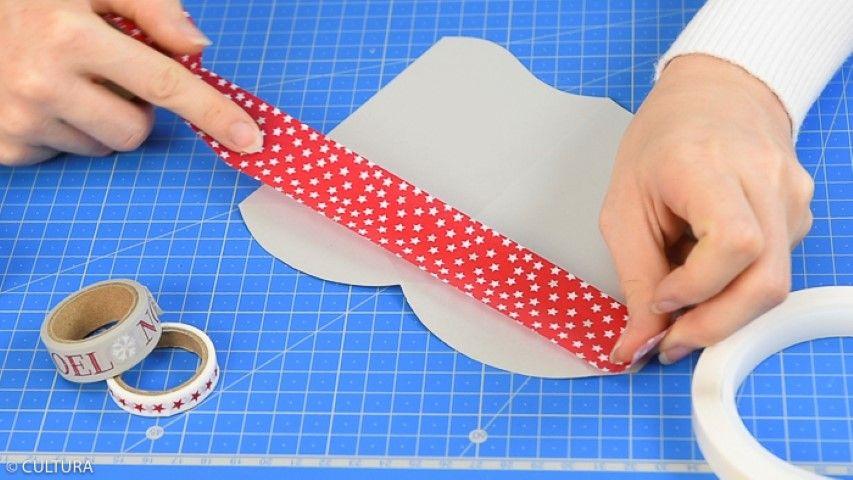 2. Coller du masking tape pour décorer la partie basse du range-serviette. Le monter et coller les languettes. Laisser sécher. Enrouler la partie basse de ficelle bicolore argentée et coller une forme de découpe de la collection.