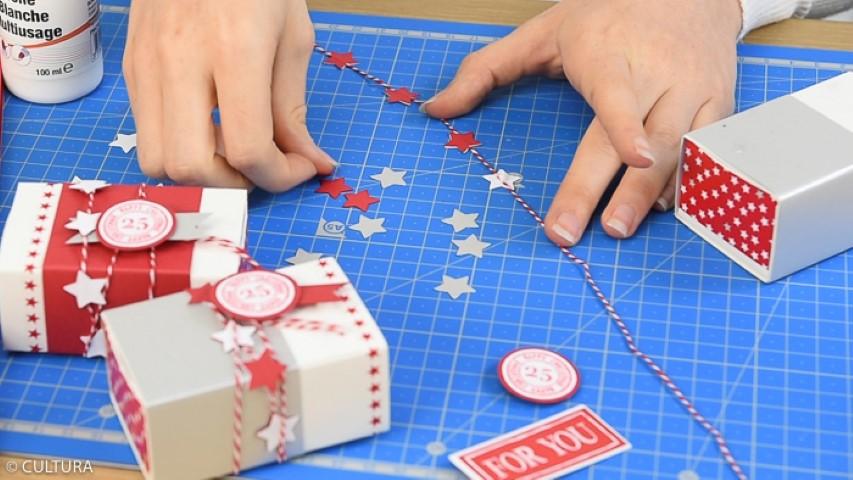 Création des cadeaux d'invités : Perforer des petites étoiles et créer une guirlande à l'aide de la ficelle bicolore pour l'enrouler autour des boîtes. Les personnaliser avec du masking tape, des papiers et des formes de découpes.