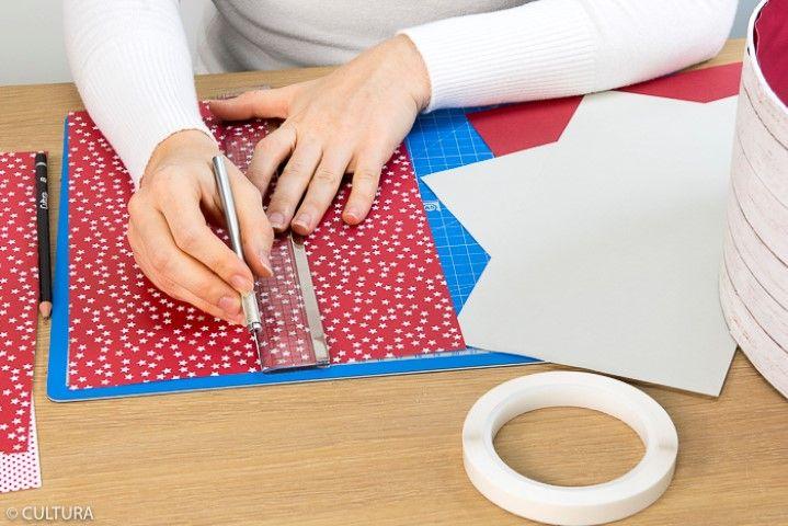 4. Découper les papiers de la collection pour créer des bandes de 15 x 29,7 cm. Les coller sur le contour de la boîte et veiller à créer les raccords. Choisir un autre motif de papier pour décorer l'intérieur de la boîte. Répéter cette action pour toutes les boîtes en variant les papiers choisis.