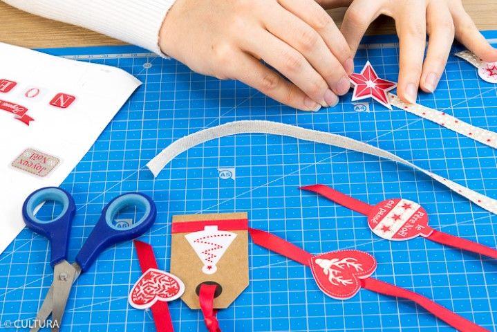 Idée n°3 : Pour créer des pampilles, couper une longueur de ruban (environ 50 cm) et coller des accessoires décoratifs aux extrémités puis les nouer autour des étoiles. Suspendre des étiquettes personnalisées de stickers. Idée + : disposer à l'intérieur des boites du papier de soie pour présenter les cadeaux.