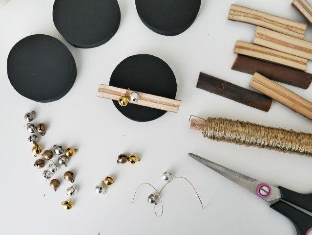 N°3 |  Couper une longueur de fil de fer coloris or, y enfiler deux grelots et enrouler autour d'un bout de bois, coller sur un côté d'un couvercle. Répéter l'action pour obtenir 5 couvercles décorés.