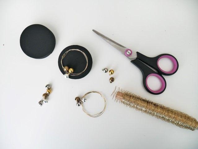 N°5 | Couper une longueur de fil de fer coloris or, y enfiler trois grelots, puis enrouler le fil sur lui-même en rond pour former une couronne, faire attention que la couronne soit légèrement plus petite que l'a taille du couvercle. Coller sur un couvercle. Répéter l'action pour obtenir 5 couvercles décorés.