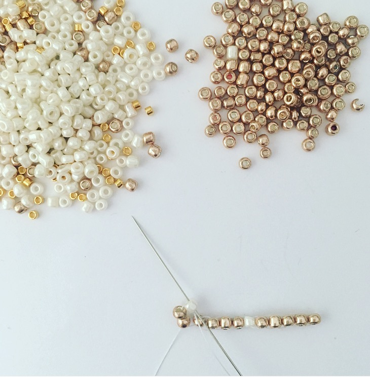 Repasser l' aiguille de bas en haut dans la 2ème perle. Les deux perles viennent se positionner au-dessus du premier rang.