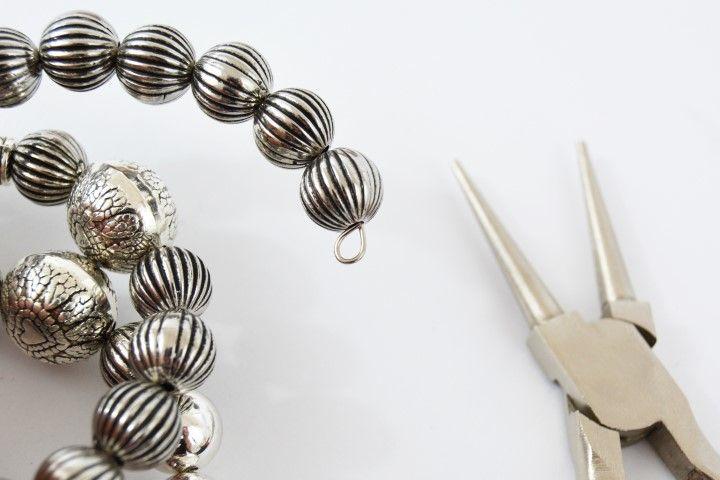 2. Pour créer des breloques à suspendre au bracelet, enfiler une perle sur un clou a œil. Créer une boucle sous la perle avec le clou et la pince ronde et insérer dans cette dernière un mini pompon. Couper à l'aide de la pince coupante l'extrémité du clou restante. Enfiler les différentes breloques entre deux perles.
