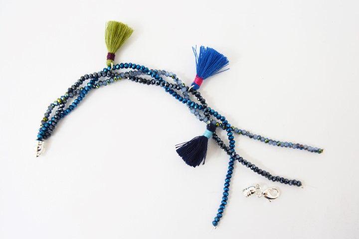 2. Tresser les liens en veillant à placer les pompons harmonieusement.