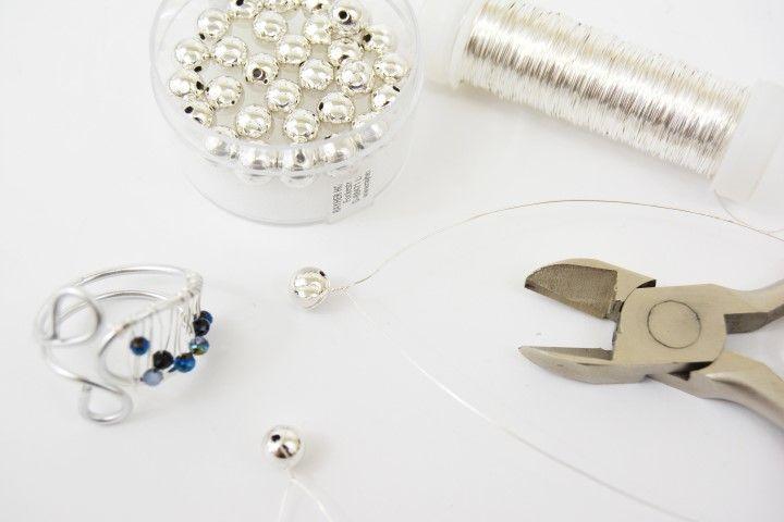 5. Couper 2 longueurs de fil métallique et insérer une perle ronde sur chacune. Torsader le fil sur lui-même pour bloquer la perle.