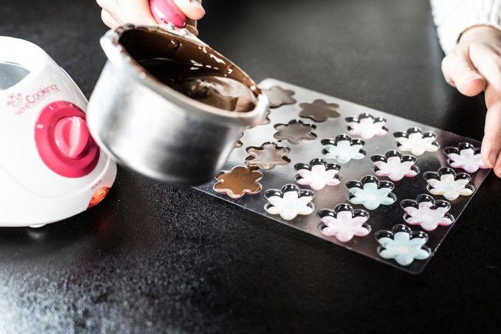 3. Moulage des petits chocolats de garnitures « fleurs » : Verser une petite quantité de chocolat dans les moules transferts. Tapoter pour bien répartir le chocolat. Réserver au frais .