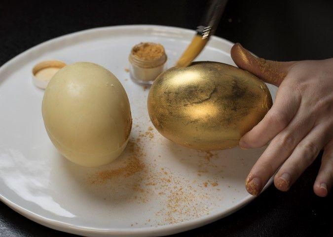 10. Idée plus : Faire des coques en chocolat blanc , au lait … A l'aide d'un pinceau de cuisine souple, répartir de la poudre d'or sur les oeufs .