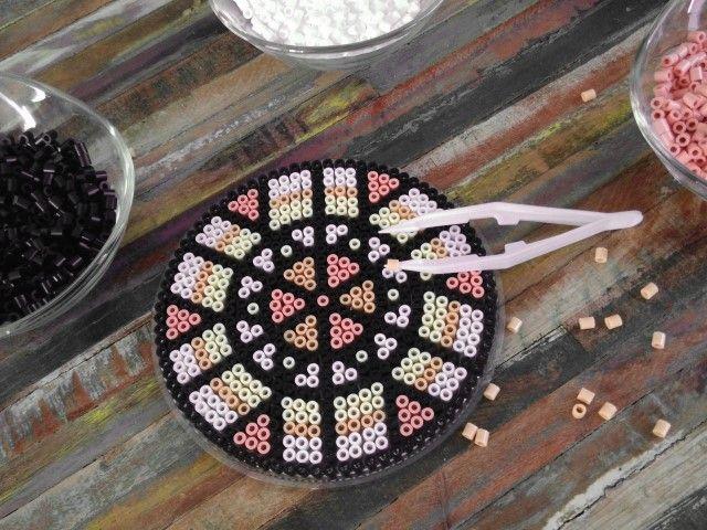 1. Réaliser la base de l'attrape rêve à l'aide d'une plaque ronde, des perles à repasser aux coloris choisis. Positionner les perles en suivant le schéma de la photo ci-dessus. Repasser le projet en positionnant la feuille de papier dessus. Les perles vont se coller entre elles par la chaleur du fer.