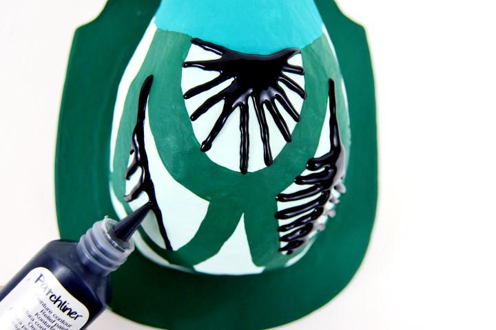 3. Dessiner des lignes graphiques à l'aide du cerne de penture relief patchliner noir réglisse sur les motifs plumes. Laisser sécher.