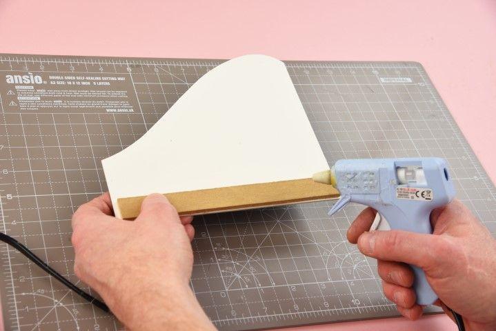 5. Coller une réglette en bois au dos de la plaque en utilisant le pistolet à colle.  Astuce: créer une réglette avec du carton mousse