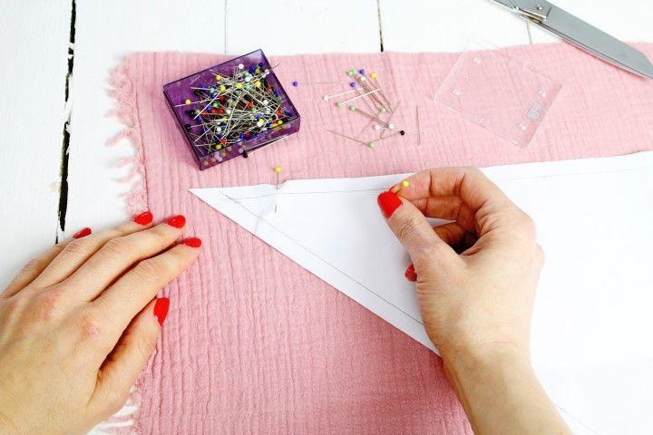 1. Pour le foulard fille, télécharger, imprimer et découper le patron (un triangle et une bande). Epingler le triangle sur le tissu double gaze Ballerine et couper. Couper une bande de tissu coton Ethnique vert pour créer le ruban central.