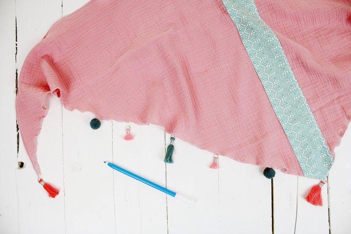 12. Pour les deux foulards, placer les pompons en mettant des petits repères grâce au feutre effaçable. Pour le foulard fille, mettre les 3 pompons 45 mm corail aux 3 extrémités. Puis sur les deux côtés mettre au centre un pompon 45 mm vert sauge et de part et d'autre un pompon 20 mm rose bonbon et un pompon rond 20 mm vert sauge. Pour le foulard maman, mettre les 3 pompons 90 mm vert émeraude aux 3 extrémités du foulard. Puis sur les deux côtés mettre au centre un pompon 45 mm bleu foncé et de part et d'autre un pompon rond 20 mm prune et un pompon rond 20 mm marine. Coudre l'ensemble des pompons.