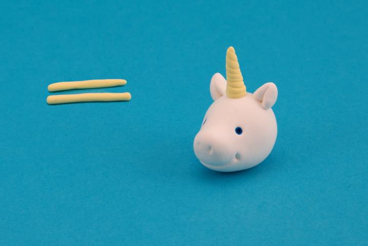 Faire deux petits boudins jaune, les tortiller ensemble puis placer la corne sur la tête.