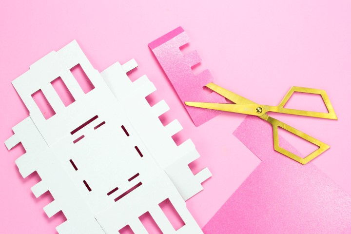 4. Tracer à l'aide d'un crayon de papier, les dessus des petits donjons sur le papier rose pailleté côté face et découper le papier à l'aide d'une paire de ciseaux.