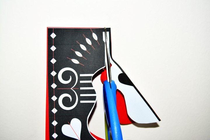 2. Positionner le gabarit sur la feuille pliée en deux avec son pli positionné du côté du motif de la guitare. Commencer à découper le contour de la guitare dans le papier origami en suivant le gabarit. Mettre le motif de la guitare de côté.