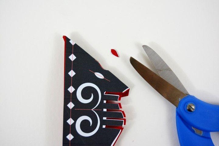 6. Plier la feuille de papier origami et le gabarit en suivant la ligne rouge de repère. Découper les petits pétales. Déplier après chaque nouvelle découpe.