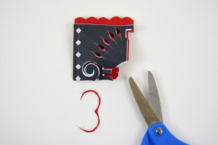 7. Plier la feuille de papier origami et le gabarit en suivant la ligne rouge de repère. Découper l'arabesque. Déplier.