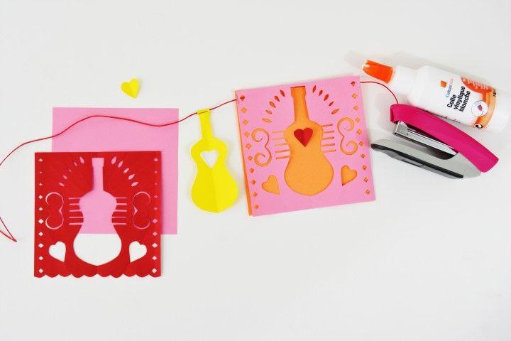 12. Pour créer une guirlande, superposer un fanion sur un papier de couleur différente et l'agrafer sur une ficelle de couleur. Coller au centre de la guitare un petit cœur de couleur différente.