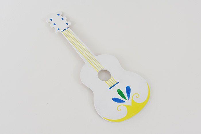 2. Créer les cordes de la guitare à l'aide d'une règle. Réaliser les lignes des cordes et le coloriage avec les marqueurs de peinture acrylique brillante.