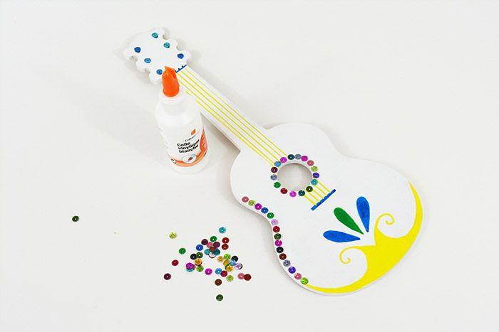 3. Pour finaliser la décoration, coller les sequins sur le contour de la guitare, les boutons de la tête et la rosace.