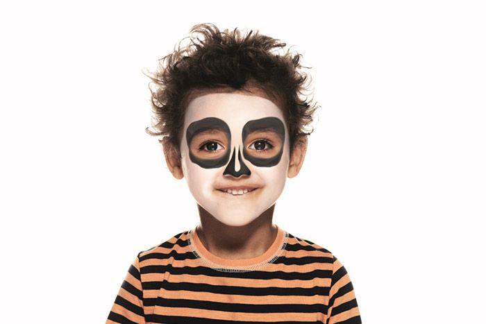 2. Prenez une éponge et dessinez deux ronds noirs autour des yeux pour représenter les orbites de la tête de mort. Ensuite, tracez deux formes pointues sur le nez, plus fines en haut qu'à la base.