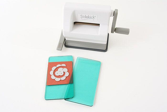 1. Découper un carré de papier plus grand que la forme de découpe. Placer le carré de papier sur la plaque, superposer la forme de découpe et replacer une seconde plaque par-dessus. Astuce : Fixer la ventouse sur le plan de travail à l'aide de la poignée sur le côté gauche de la machine.