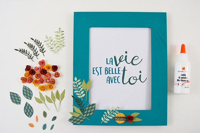 2. Coller les embellissements papiers, les feuillages et les roses harmonieusement sur le cadre. Télécharger et imprimer le texte pour l'insérer dans le cadre à offrir.