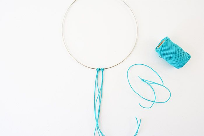 1. Couper 3 longueurs de fil macramé wax d'environ 60 cm et les nouer autour de la torque de façon à obtenir 6 longueurs d'environ 30 cm.