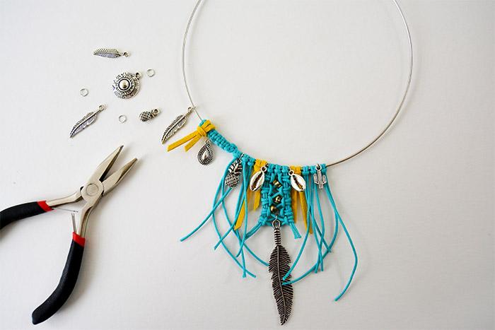 10. Couper une longueur de suédine et la nouer sur le tressage. Insérer un anneau sur chaque breloque choisie et les insérer sur la torque.