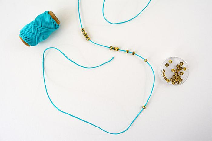 1. Couper plusieurs mètres de fil en fonction du nombre de tours souhaités autour du chapeau. Insérer des perles de rocailles et les éparpiller sur le fil.