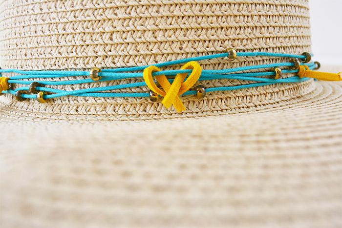 3. Couper des petites longueurs de suédine et les nouer sur le fil autour du  chapeau en laissant un espace d'une dizaine de centimètres environ.