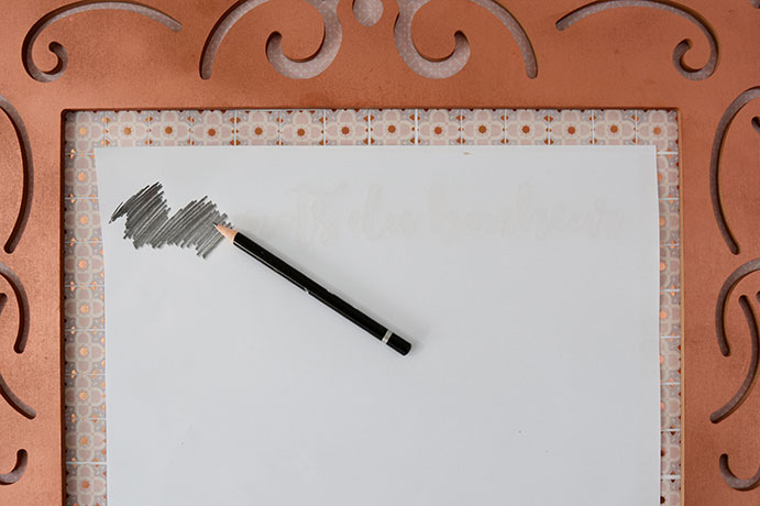 ETAPE 8/11 - Retourner et centrer le gabarit en haut du carton plume. Gratter avec un crayon le dos du lettering visible par transparence.