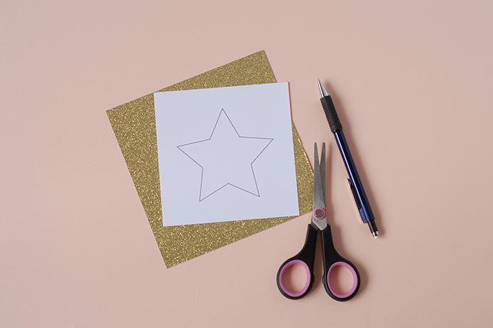 2. A l'aide du gabarit, découper 2 étoiles dans la feuille de papier glitter or.
