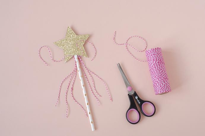 6. Coller l'étoile sur la paille au dos de l'autre étoile. Prendre 2 morceaux de ficelle et faire un noeud.