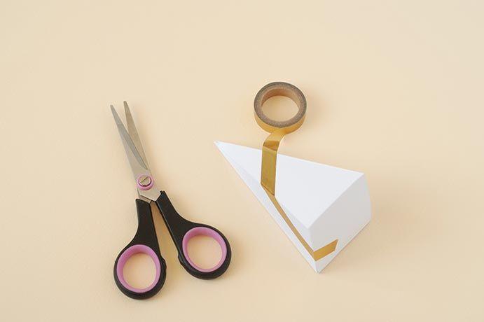 2. Monter le cône. Coller le masking tape sur le haut de la boite et commencer à enrouler autour du cône.
