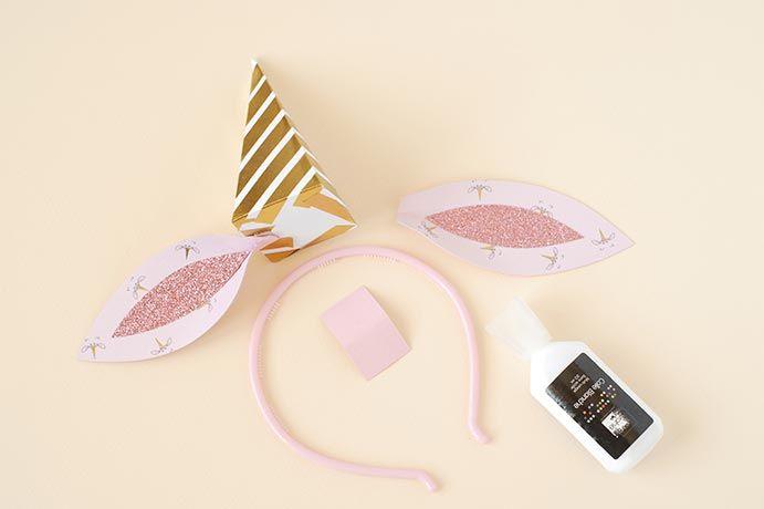 5. Coller les oreilles en papier licorne sur le papier rose blush. Coller ensuite l'intérieur des oreilles. Découper dans le papier rose blush, 1 x ( 2 x 4 cm). Fixer les oreilles au cône et fixer le tout sur le serretête à l'aide du papier rose.