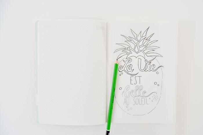 2. Retourner le papier calque et le positionner centré sur une page du carnet. Repasser sur chaque tracé par transparence : le motif se décalque sur le papier.