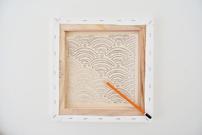 2. Retourner le papier calque et le positionner centré au dos de la toile. Repasser sur chaque tracé par transparence : le motif se décalque sur la toile.