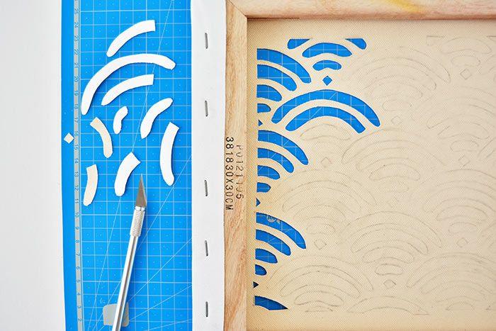 3. Positionner la toile sur un tapis de découpe et entailler minutieusement chaque motif à l'aide d'un cutter de précision.